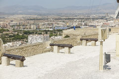 Cannons in the fortress. Line of ancient cannons in the rampart of the castle of santa barbara with the city of alicante, spain in teh background Stock Photos