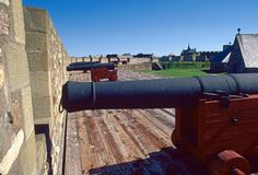 Cannons at historic site. Row of cannons by a protective brick wall in the Fortress of Louisbourg, a historic site in Nova Scotia, Canada stock photo
