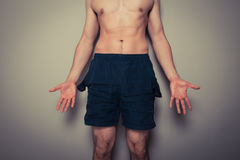 Cannot afford the gym. Athletic young man with empty pockets cannot afford to go to the gym Royalty Free Stock Images