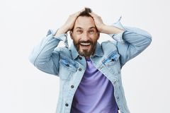 Cannot believe it happen to me. Joyful happy and excited caucasian male model, touching hair and smiling broadly while. Gazing with satisfaction and amusement stock images