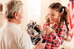 Charming preteen kid examining robotic machine. Cannot keep my emotions ine. Adorable little girl grinning broadly while standing next to her grandfather and Stock Photo