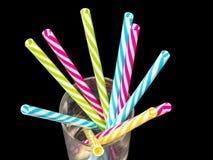 0614 cannucce di plastica colorate differenti disposte in un fondo nero di vetro jpg fotografie stock