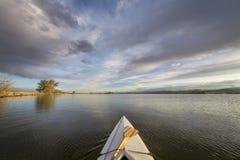 Canoë avec une palette sur le lac Photos stock