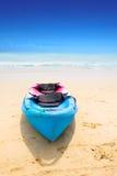 Canoë bleu et rouge par une plage sablonneuse Photographie stock libre de droits