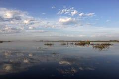 Canoë dans un lac avec des nuages reflétés Photos stock