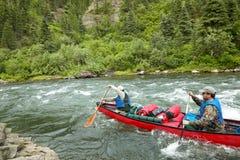 Canoë-kayak d'hommes sur la rivière turbulente en Alaska sauvage Photo libre de droits