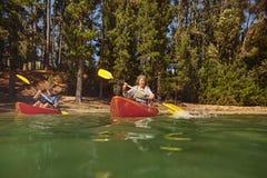 Canoë-kayak mûr de couples sur un lac pendant des vacances en camping Photographie stock