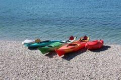 Canoë multicolore sur le rivage de lac Photo libre de droits