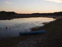 Canoë par le lac au coucher du soleil Photos libres de droits
