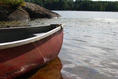 Canoë rouge avec le soleil réfléchissant sur la poupe outre de l'eau Images libres de droits