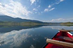 Canoë rouge dans le lac Photo stock