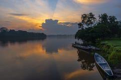 Canoës au coucher du soleil dans le bassin du fleuve Amazone, Equateur photographie stock libre de droits