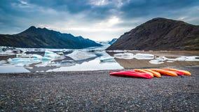 Canoës au lac glaciaire froid dans les montagnes, Islande images libres de droits