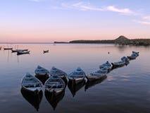 Canoës dans le coucher du soleil Photo stock