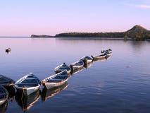 Canoës dans le coucher du soleil   photos libres de droits