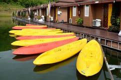 Canoës/kayaks jaunes et roses dans une rangée sur le bord de l'eau Photos stock