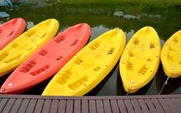 Canoës/kayaks jaunes et roses dans une rangée sur le bord de l'eau Photographie stock libre de droits