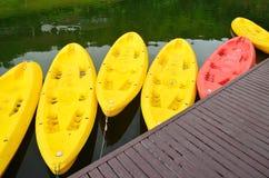 Canoës/kayaks jaunes et roses dans une rangée sur le bord de l'eau Image stock