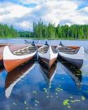 Canoës réfléchis sur un lac canadien photos stock