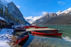 Canoës rouges chez Lake Louise avec la montagne rocheuse en parc national de Banff photo libre de droits