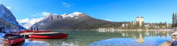 Canoës rouges chez Lake Louise avec la montagne rocheuse en parc national de Banff photographie stock libre de droits