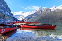 Canoës rouges chez Lake Louise avec la montagne rocheuse en parc national de Banff image libre de droits