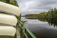 Canoës stockés sur un support donnant sur un lac en automne image libre de droits