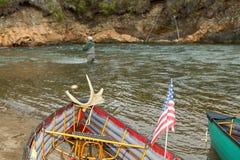 Canoës sur la pêche de mouche de banque et d'homme à l'arrière-plan image stock