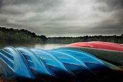 Canoës sur la plage au lac orageux photographie stock
