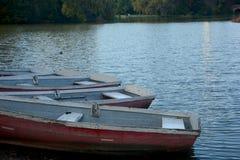 Canoës sur le rivage d'un lac au crépuscule photographie stock