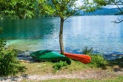 Canoës sur le rivage du lac photo stock