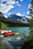 Canoës sur un dock au beau lac vert images stock