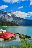 Canoës sur un dock au beau lac vert images libres de droits