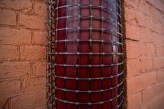 Cano em uma grade protetora em uma parede de tijolo Fotografia de Stock