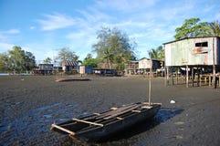 Canoa alla costa del fiume del villaggio Fotografia Stock