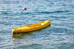 Canoa amarela e um flutuador vermelho no mar azul fotos de stock royalty free