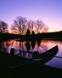 Canoa amarrada por un lago crepuscular Fotografía de archivo