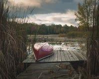 Canoa de cabeça para baixo em uma doca Foto de Stock Royalty Free