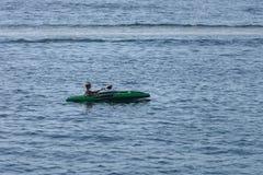 Canoa del giovane nel mare Immagini Stock
