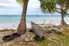 Canoa di intelaiatura di base della gru polinesiana tradizionale in cima alle vecchie gomme su un roccioso immagine stock