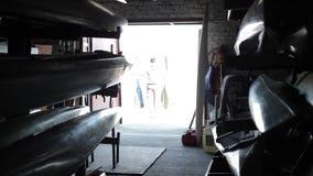 Canoa e caiaque Um homem sae do armazém com uma pá em suas mãos da escuridão na luz vídeos de arquivo