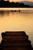 Canoa en el lago en la puesta del sol Fotos de archivo