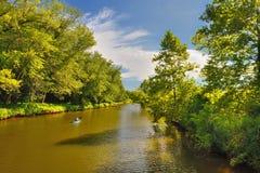 Canoa, flutuando abaixo do rio através das árvores Fotos de Stock Royalty Free