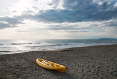 Canoa gialla su una spiaggia sabbiosa vicino al mare Immagini Stock