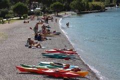 Canoa multicolora en la orilla del lago Fotografía de archivo