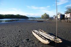 Canoa na costa do rio da vila Foto de Stock Royalty Free