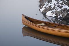 Canoa nova que flutua na água calma no por do sol do inverno Fotografia de Stock Royalty Free