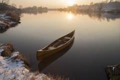 Canoa nova que flutua na água calma no por do sol do inverno Foto de Stock Royalty Free