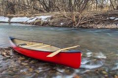 Canoa roja en un río Imagen de archivo libre de regalías