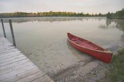 Canoa rossa tirata sul lago Immagini Stock Libere da Diritti